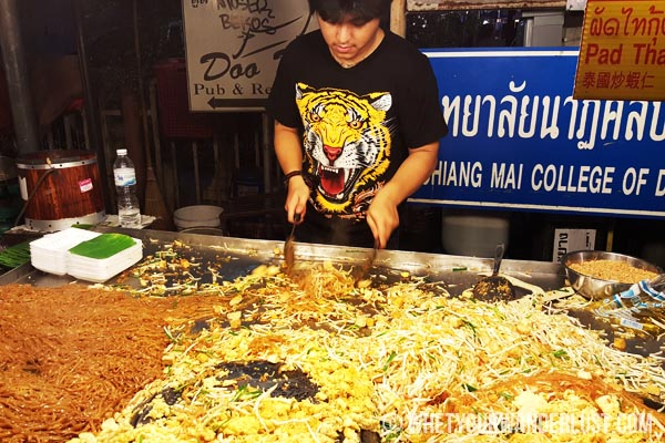 Street food with man in tiger shirt cooking pad thai in Chiang Mai